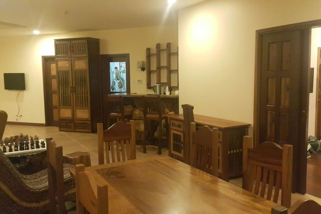 Custom old wood furniture and carvings, dining table, chess area, sala with TV and mini bar