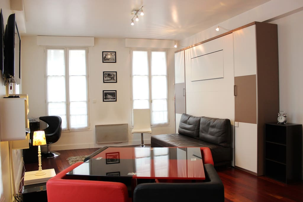 The living room has five large windows to illuminate this apartment. It is equipped with a dining table for four people, sofa, murphy bed, coffee table, cable, TV, DVD, desk, armchair, built-in wall closet, home cinema, hard wood floor.