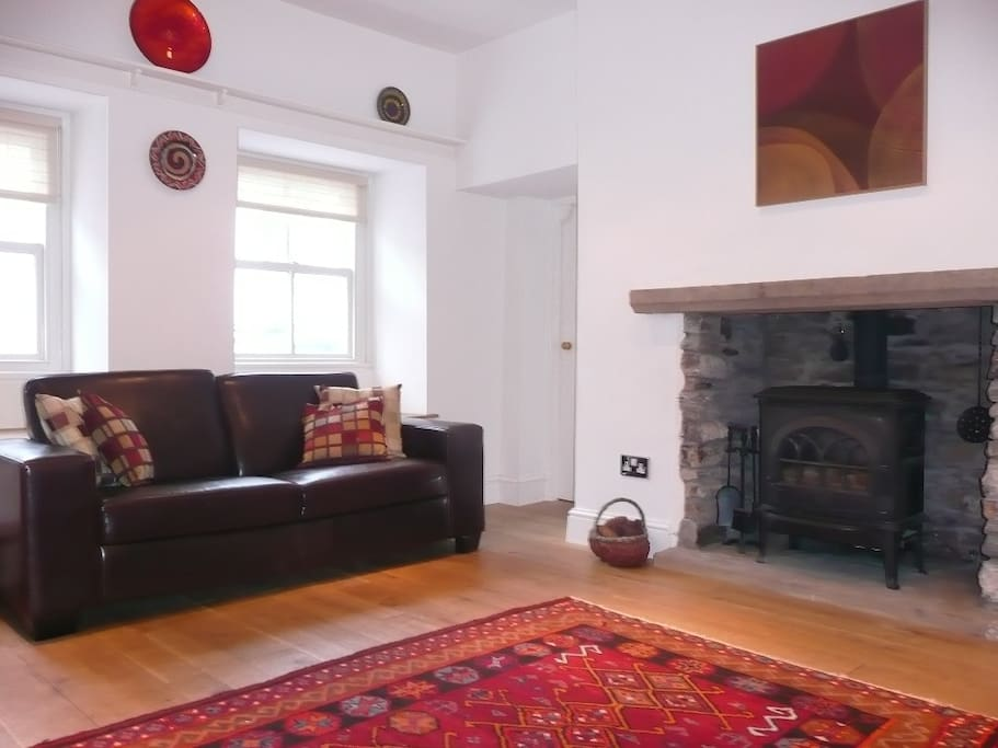 There is a spacious living room with a traditional coal effect stove.