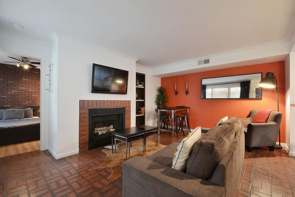 A queen-size sleeper sofa sits opposite a flat-screen TV with cable and decorative fireplace in the living room.