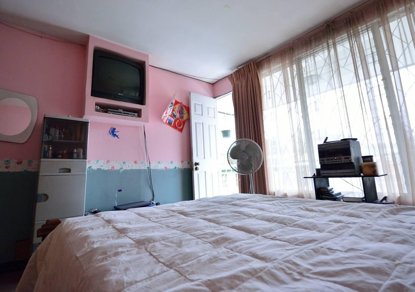 Queen bed in one of the rooms with tv and balcony