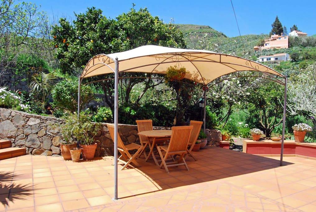 Terraza con mobiliario para exterior y pérgola