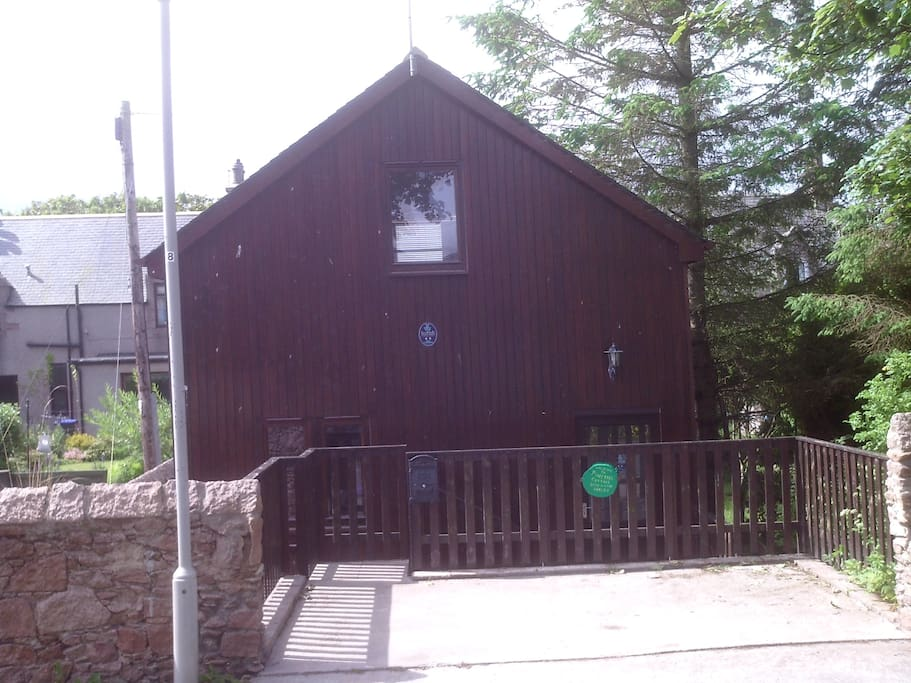 FRONT OF CHALET WITH PARKING AREA AND ACCESS TO ROAD .