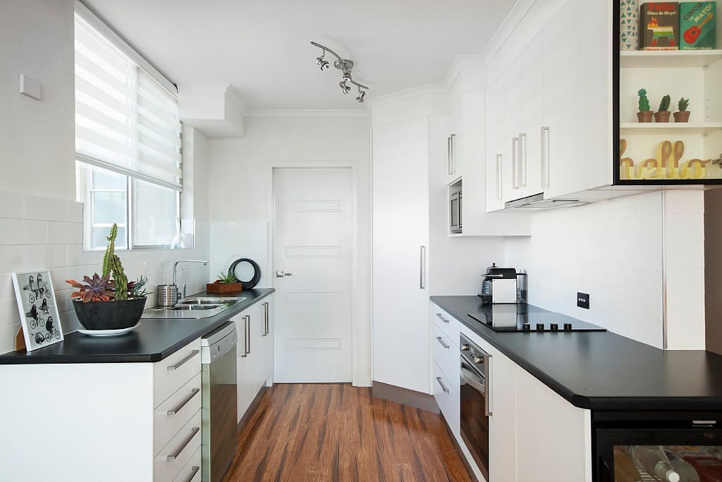 Modern kitchen with fridge, cooking facilities including oven/stove, dishwasher, microwave, plus all your required cooking and dining essentials.