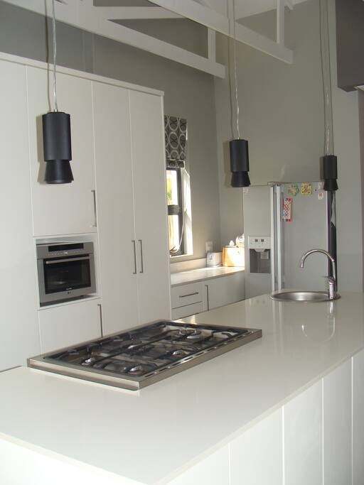 A spacious kitchen with gas stove and electric oven.