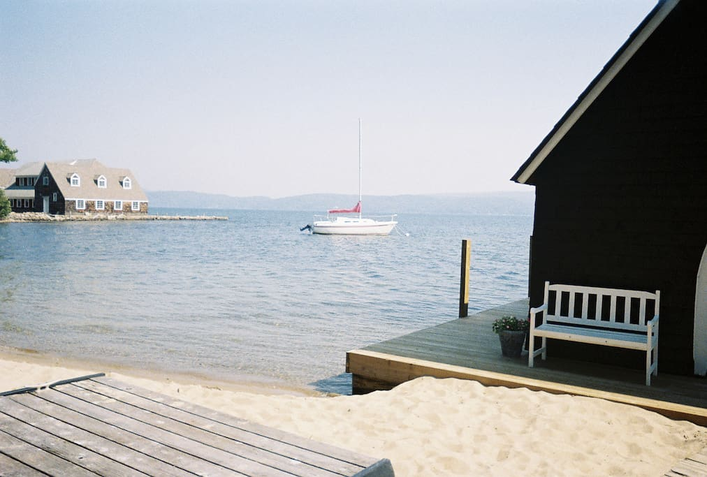 Dock and/or mooring space available.  (Sandy beach featured in foreground, boathouse on the right, boat moored in the distant and neighbor's boathouse in the far left)