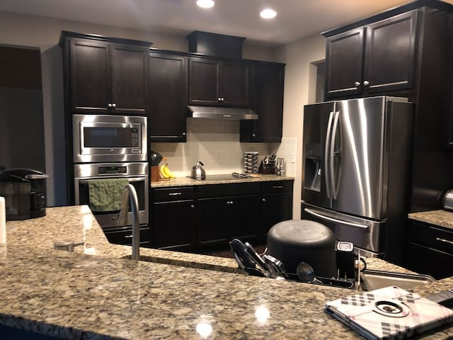 Shared space large kitchen with marble counter tops and stainless steel appliances