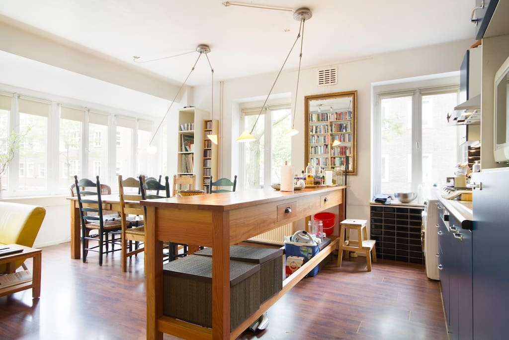Living room: dining table (left), working table and open kitchen