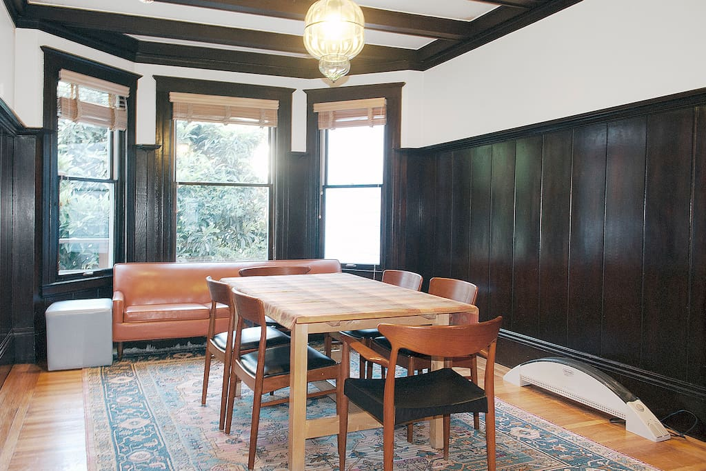 Large wood paneled dining room with expandable table great for family dinners.