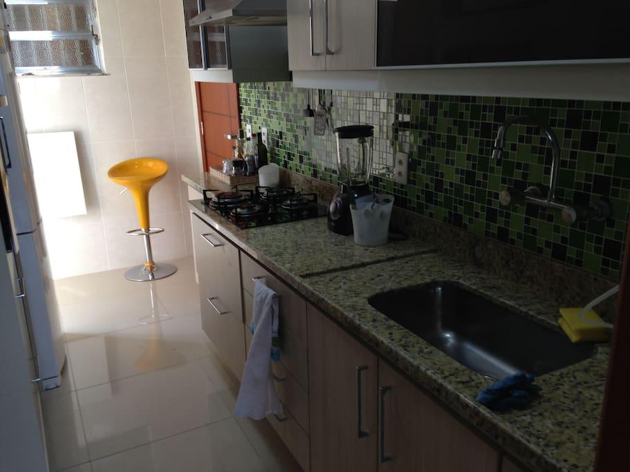 uma cozinha planejada nova, super limpa e equipada com geladeira, fogão, liquidificador, torradeira, forninho, microondas, panelas, copos, pratos e outros acessórios.