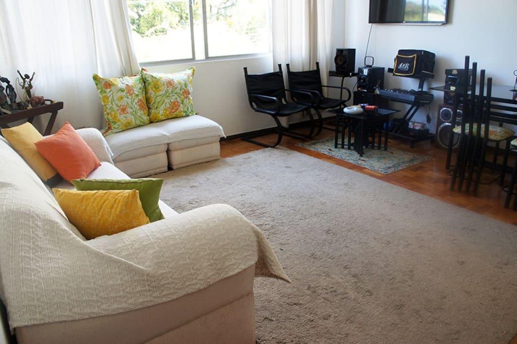 Outra vista da sala aparecendo aparelho de som e TV