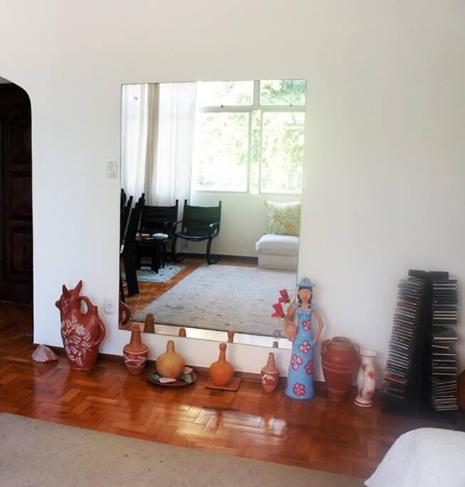 Vista da sala onde aparece espelho de parede e parte da porta de entrada