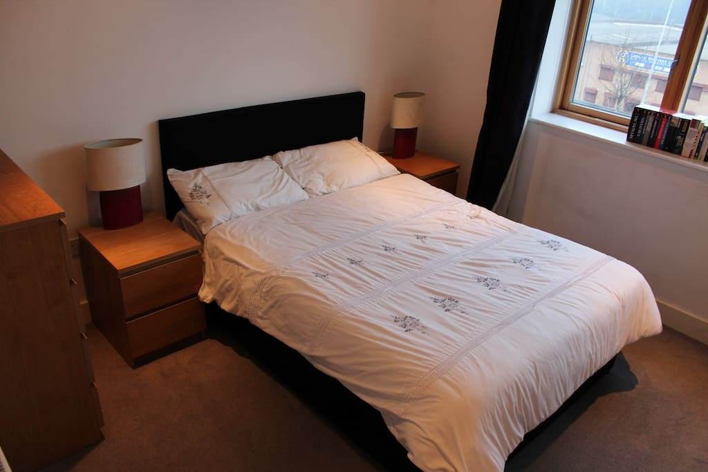 Bedroom with double bed, drawer unit, side lockers with lamps and large built in wardrobe.  Black out blinds.
