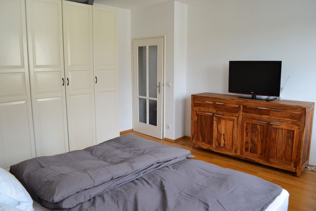 Bright bedroom with a  5 star king size luxury bed and a flat screen television