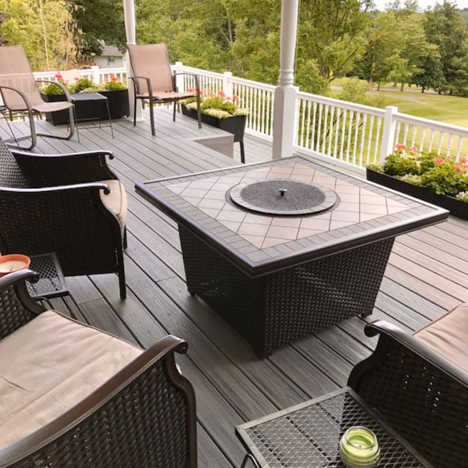 Covered deck with fireplace over looking the golf course
