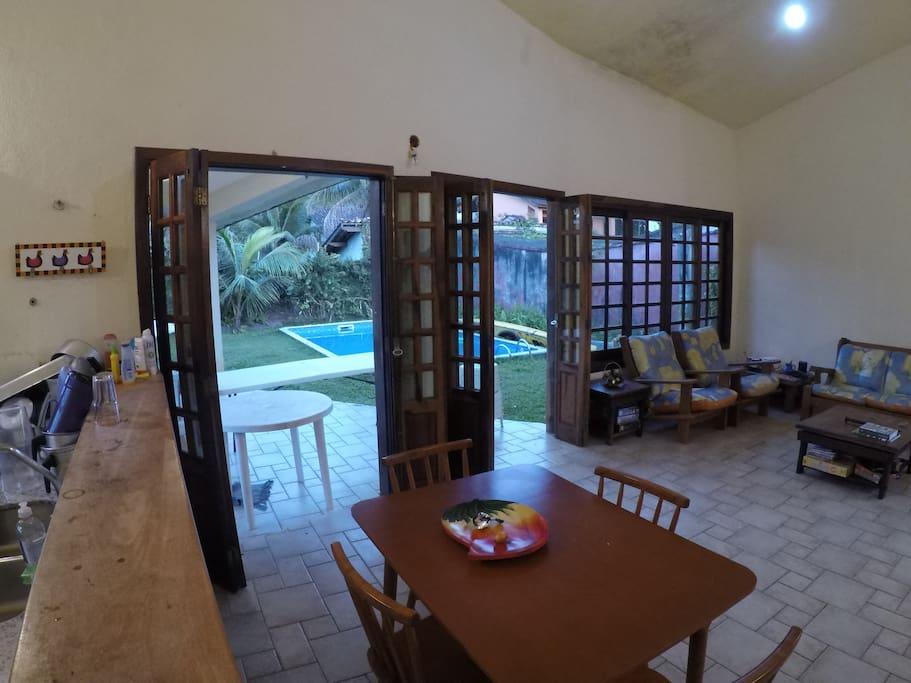 Sala aberta para a piscina e jardim