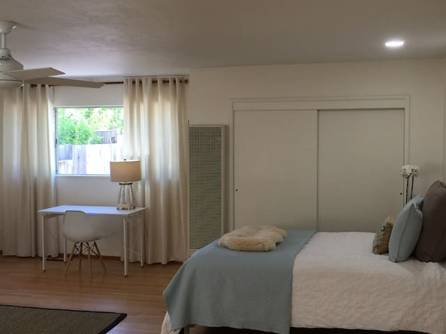 Queen-sized brand new Serta bed with sliding doors leading to a super spacious closet with shelving. The work/desk faces another gorgeous garden on the premises.