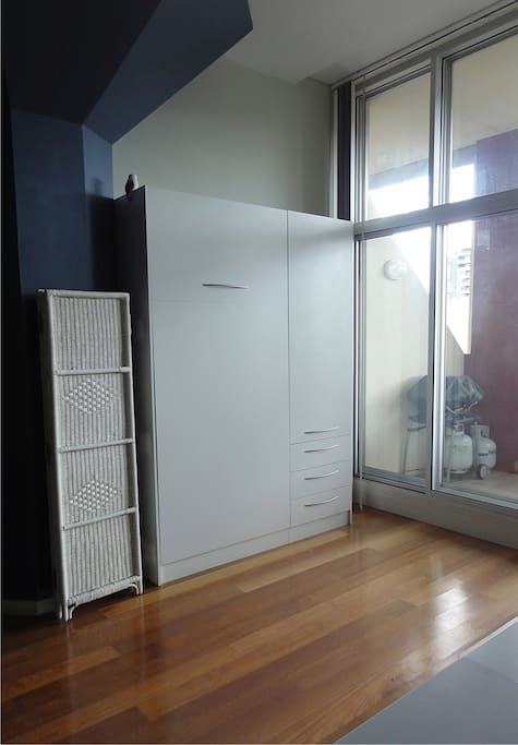 Single wall-bed in office area folds away into a cupboard