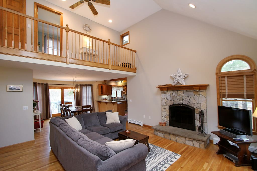 Living area includes sectional couch (seats 5), fireplace, tall ceiling,&internal balcony