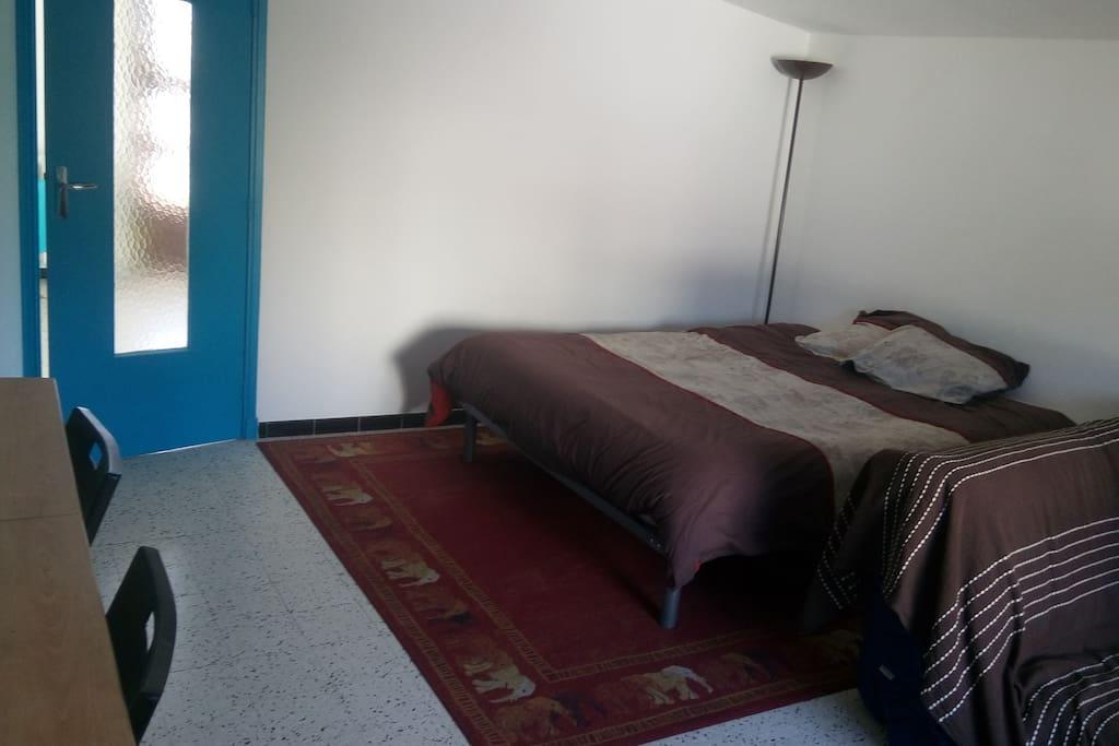La chambre, dotée, d'un grand lit, d'un canapé, d'une grande table et d'un bureau