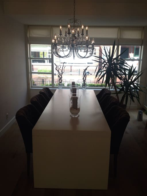 Large diner table with chandelier next to the open kitchen