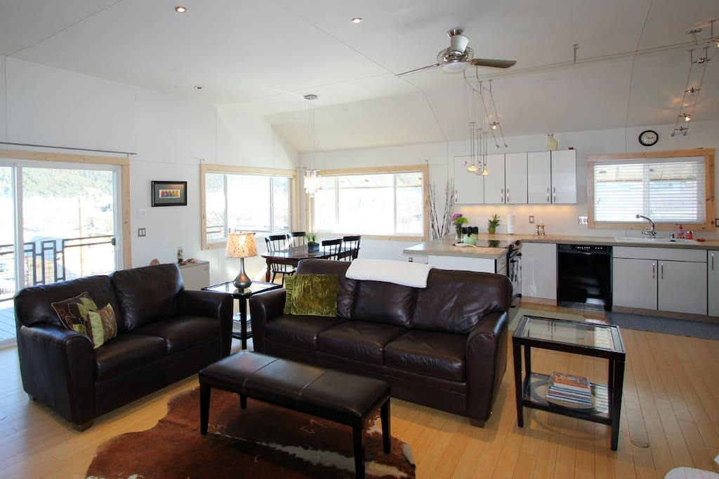 Living room,  dining and kitchen.  Sliding door goes out to deck w/ gas grill and views