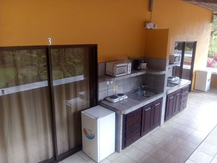 Outdoor kitchenette furnished with a mini fridge, two-electric burners, coffee maker, rice cooker and microwave!