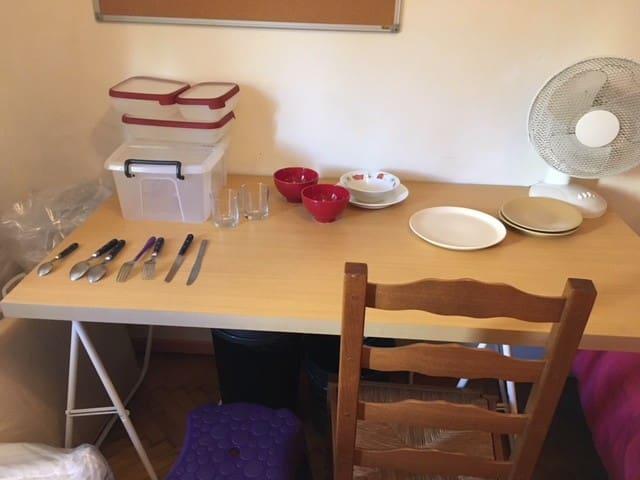Bureau + vue sur le kit des couverts (ustensiles) pour les repas qui équipent la chambre.