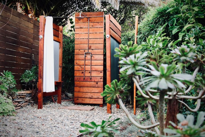 Hot shower in the garden alongside a curtain of bamboo. Handmade, copper pipe shower with a hot and cold valve. Environmentally friendly shampoos and soaps are provided. Hooks for towels and robes are within reach.