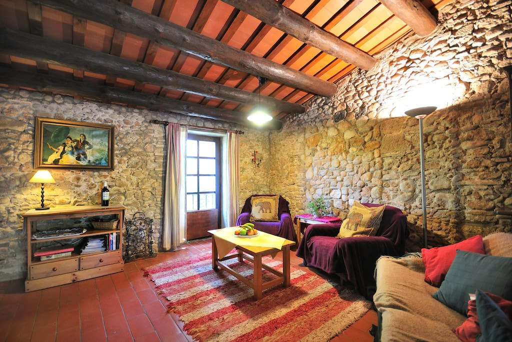 Traditional catalan style living space with original stone walls and pine beams.  South facing overlooking Sant Nicolau gardens
