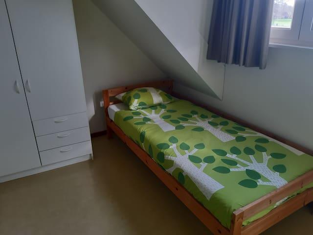Slaapkamer voorzien van 2 eenpersoonsbedden met kledingkast.