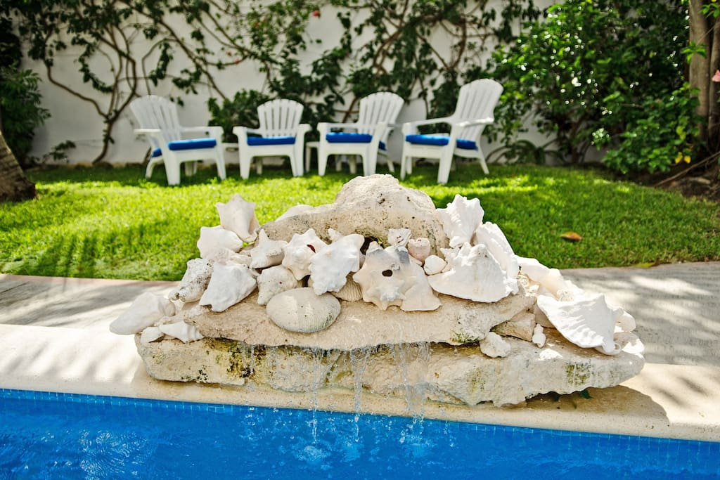Small rock fountain that cascades water into the top level of the pool