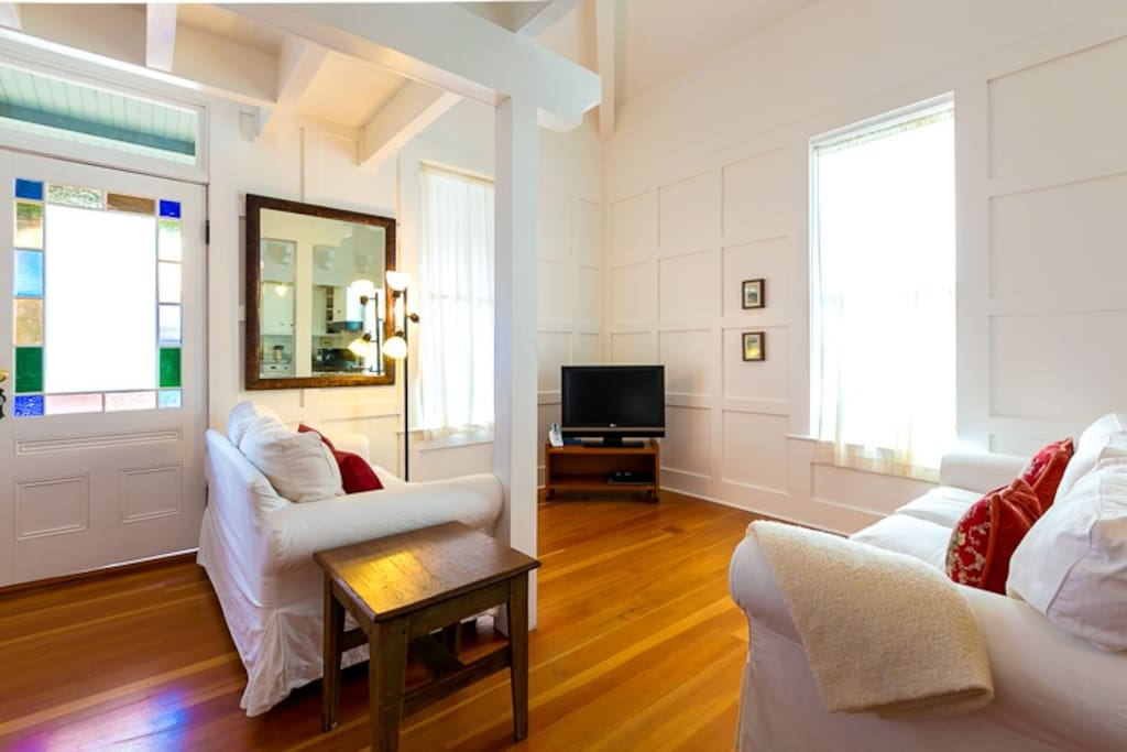 Comfortable light, bright living room area with flat screen TV.