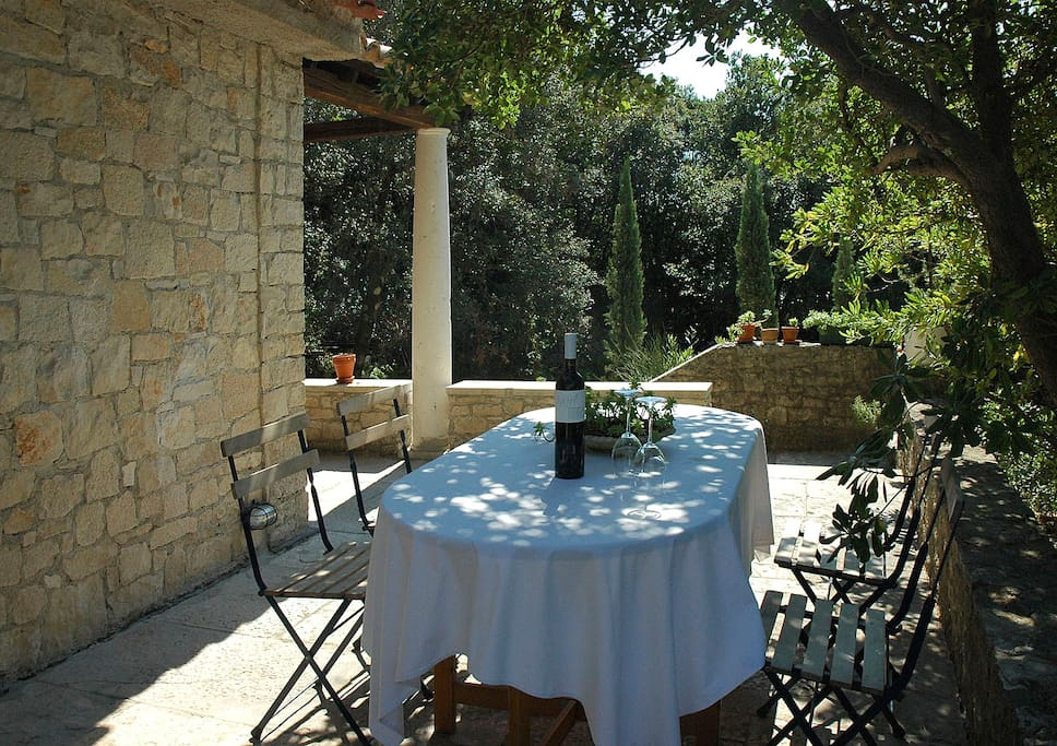 The stone cottage is surrounded by a large paved terrace