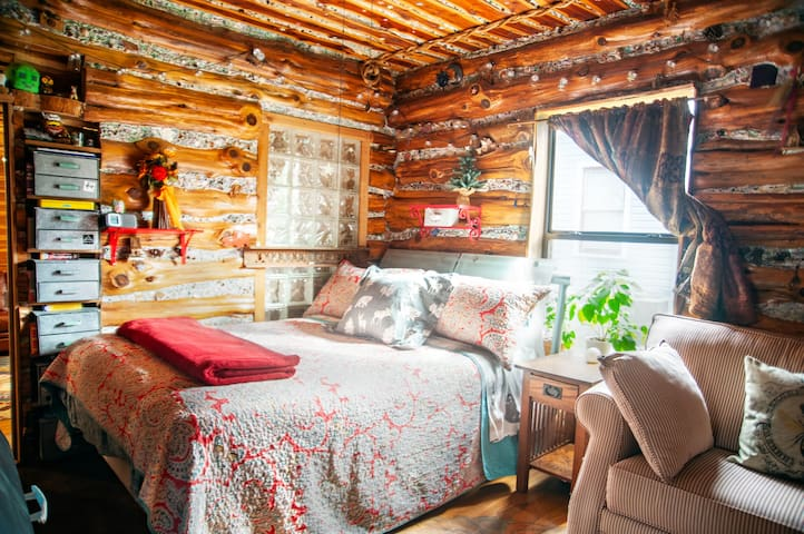 This cozy log room has a comfy  Tempurpedic queen and a hide-away twin chair. Look between the logs and you will see treasures!