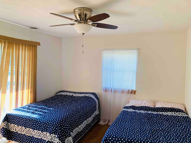 Bedroom with two double beds Room includes closet , dresser, and tv This room is downstairs