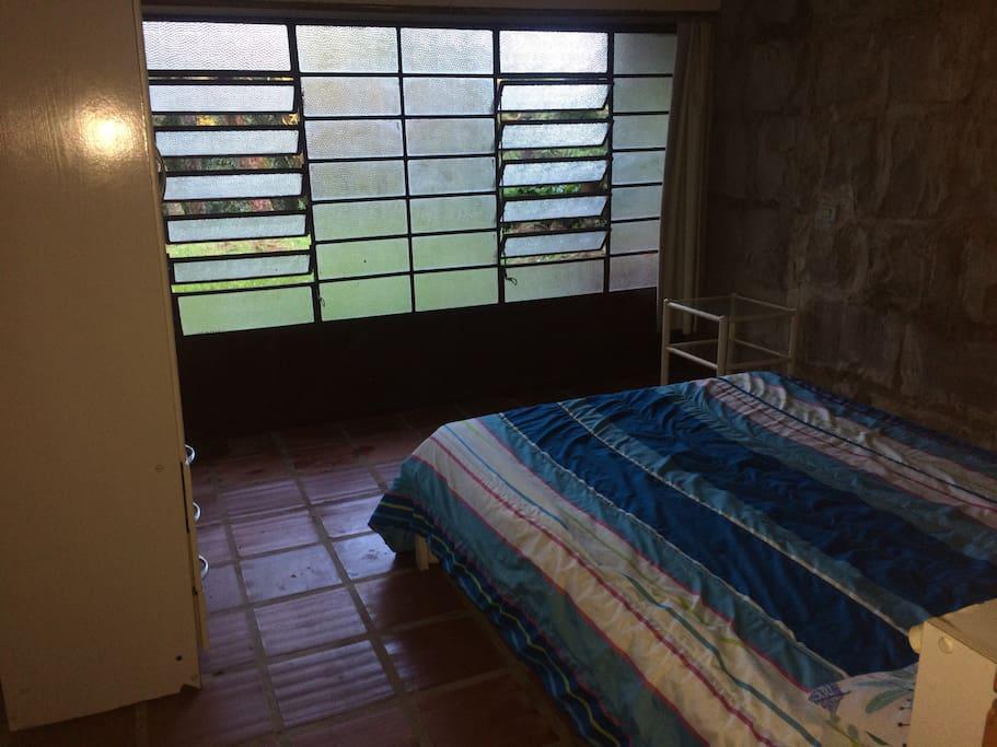 A frente da cama temos a janela panorâmica que oferece uma meia-luz durante o dia com ar fresco fornecido pela natureza. A noite pode-se fechar os vidros e a cortina e temos total privacidade e conforto para uma ótima noite de sono.