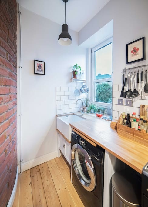 Restored, original brick wall reflects gorgeous morning light in the kitchen. Traditional heritage taps, real wood worktop and built in Belfast sink