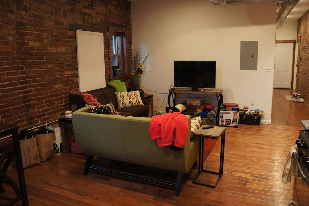 Open Living Apartment with Hardwood Floors and Exposed Brick