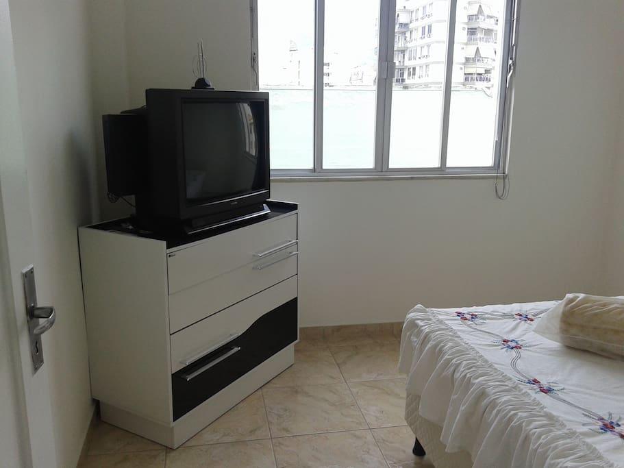Quarto secundário com ampla janela, cama casal box, cômoda e TV.