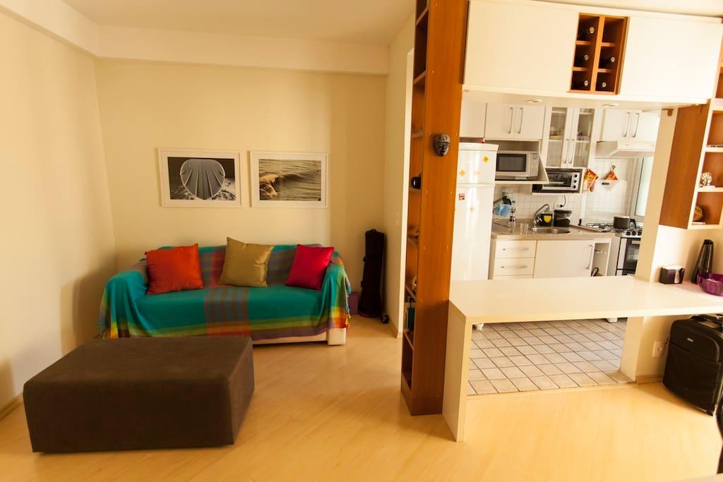 sofá em frente a tv e cozinha