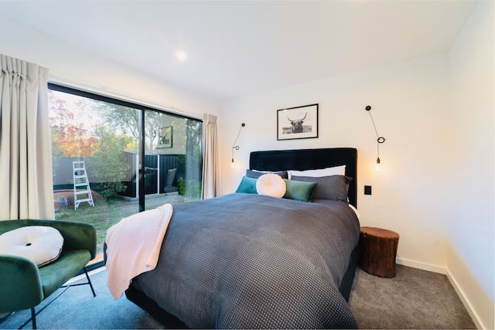 Bedroom 3, queen bed, large wardrobe, arm chair.  Opens onto the back garden.