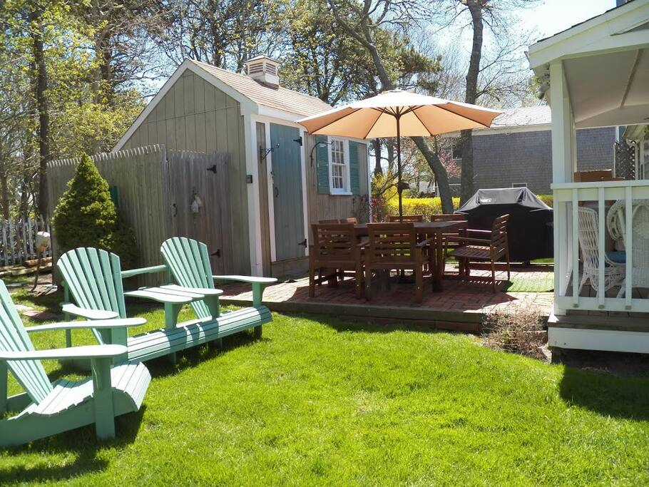 Open backyard perfect for family time and outdoor dinners complete with adirondack chairs, patio furniture, and a Weber grill!