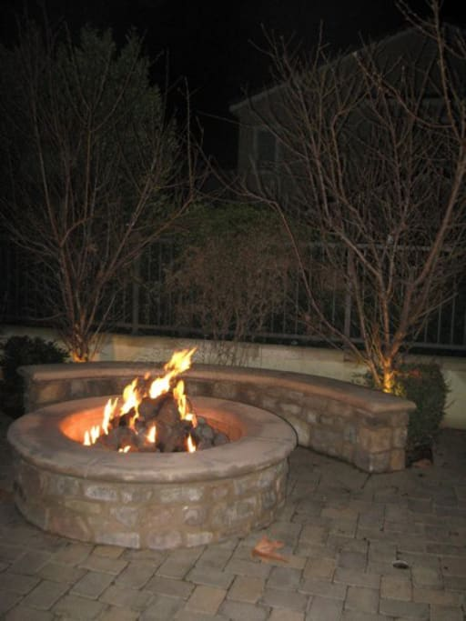 Fire pit in garden surrounded by two peach trees and hardscape bench.
