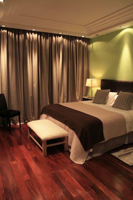 King size bed adjacent to ensuite master bath.