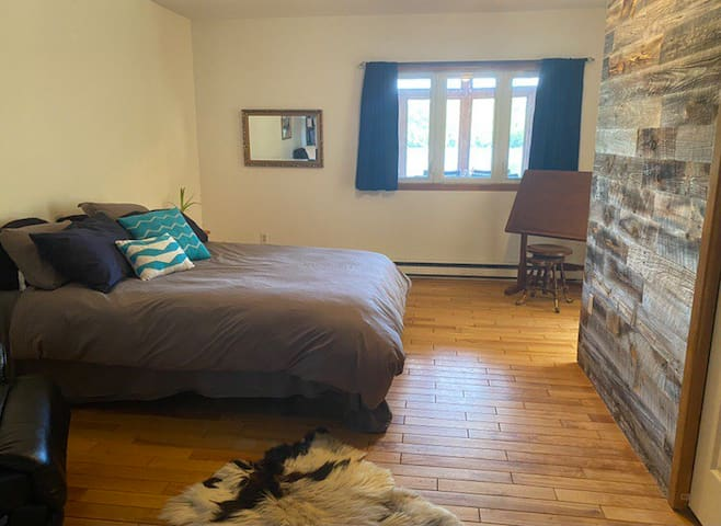 Lakeview Bedroom equipped with ceiling fan, large closet, drafting desk, reclining chair and many books