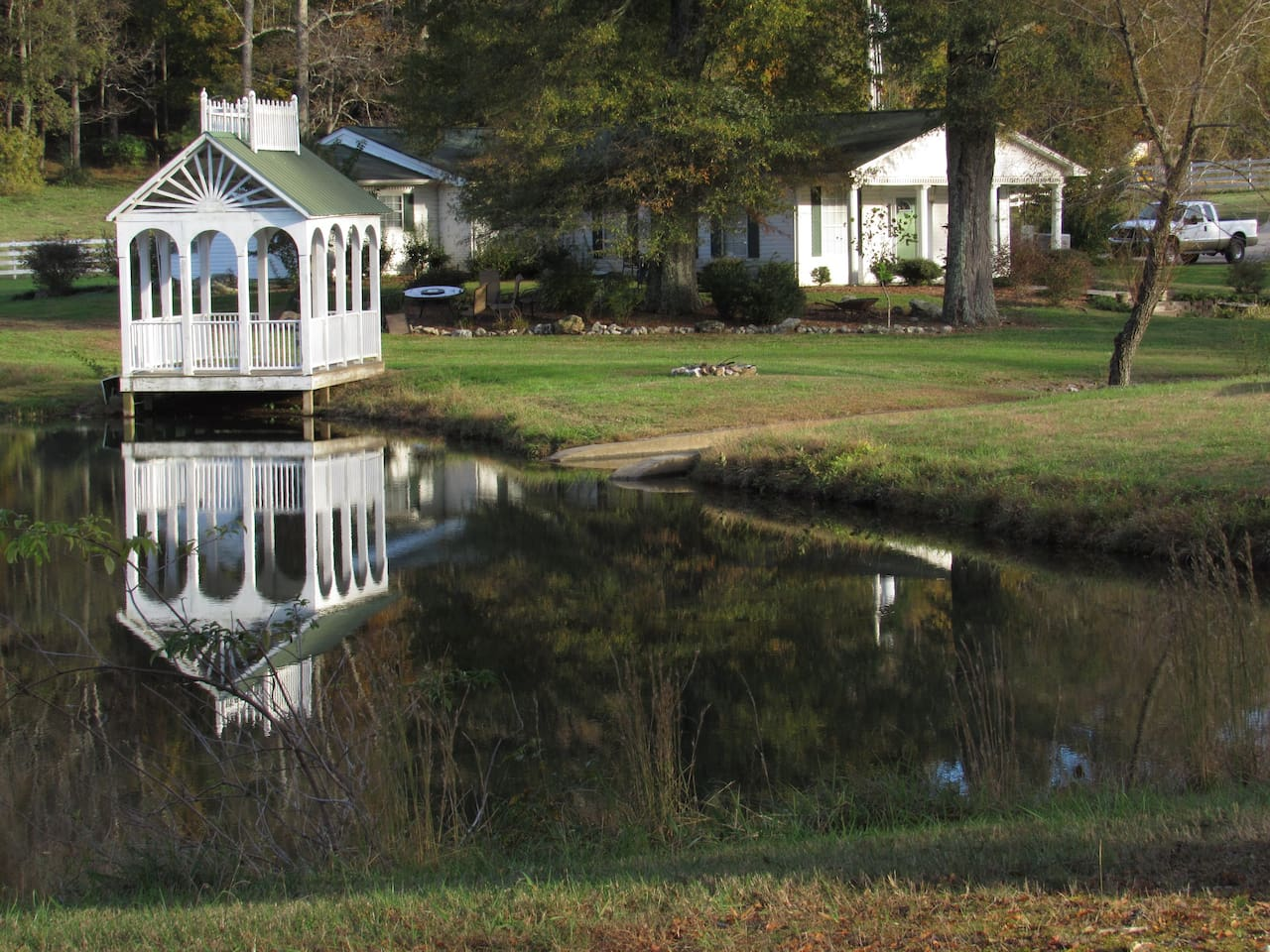 View from the driver's side as you travel down the winding driveway.  The gazebo overlooks the creek-fed lake. The single story ranch style guest house is directly in front of you once you cross over the creek spillway.