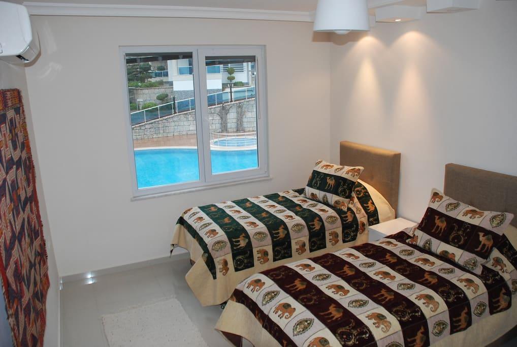 Lower floor bedroom #1. It has 2 single European beds with pool view.