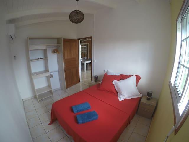 Chambre 1 climatisée lit double 140 x 190 (bonne literie) penderie + cintres moustiquaire, raquette pour moustiques linge de maison (draps et serviettes fournis), table à repasser, séchoir fenêtre sécurisée