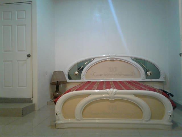 se muestra la cama  y al lado la puerta es el baño
